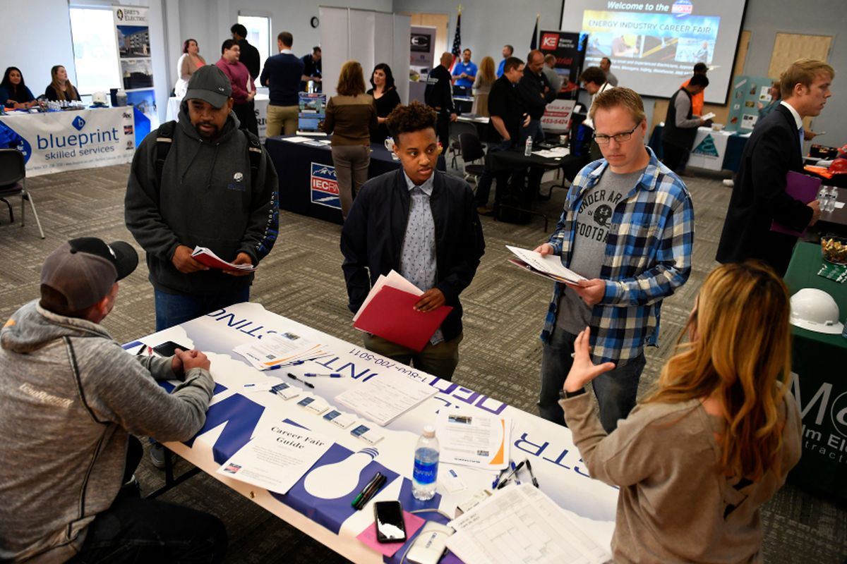 Job candidates stand around a table at a career fair.