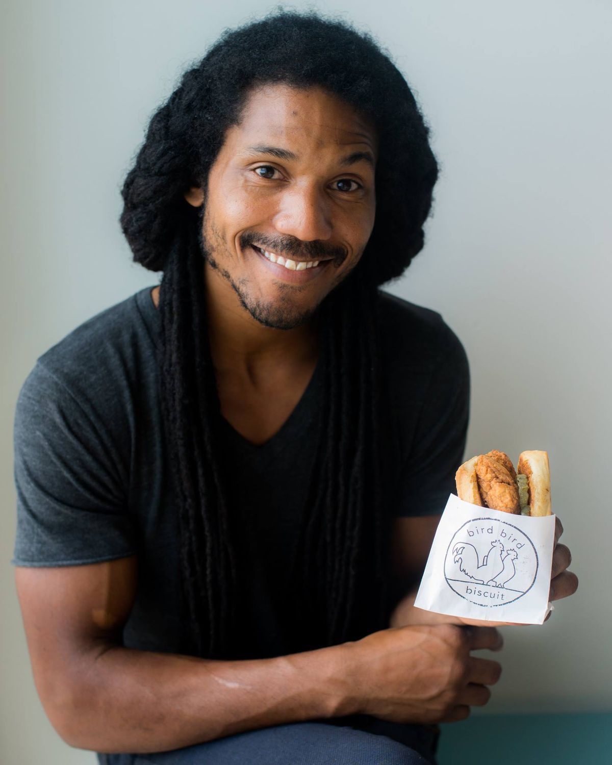 Bird Bird Biscuit co-owner and chef Brian Batch holds up a biscuit sandwich