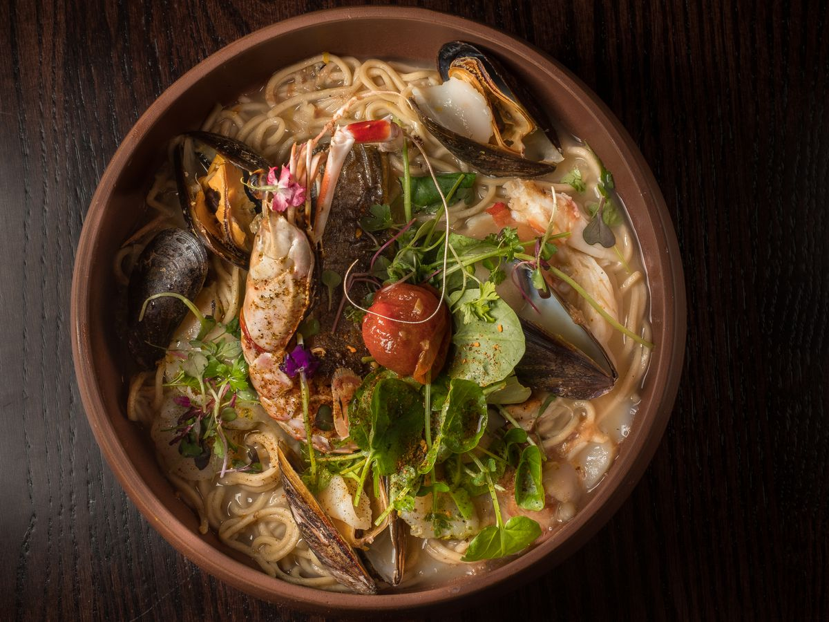 A closeup of an earthenware bowl filled with ramen, broth, and topped with half a prawn