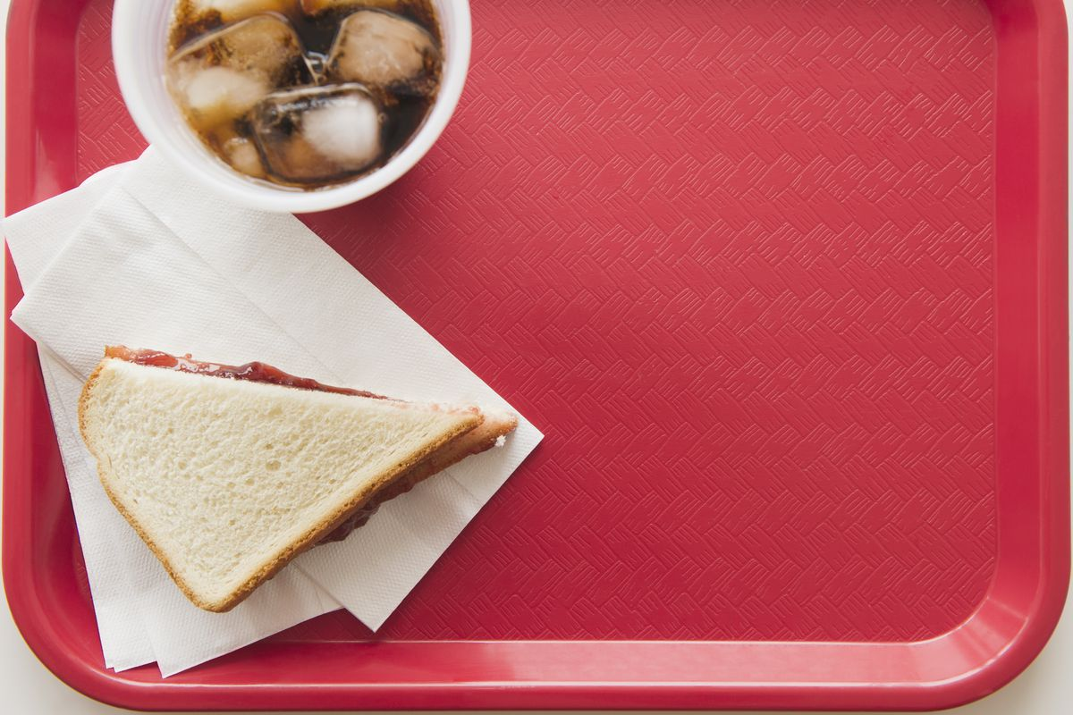 A tray with soup and a sandwich.