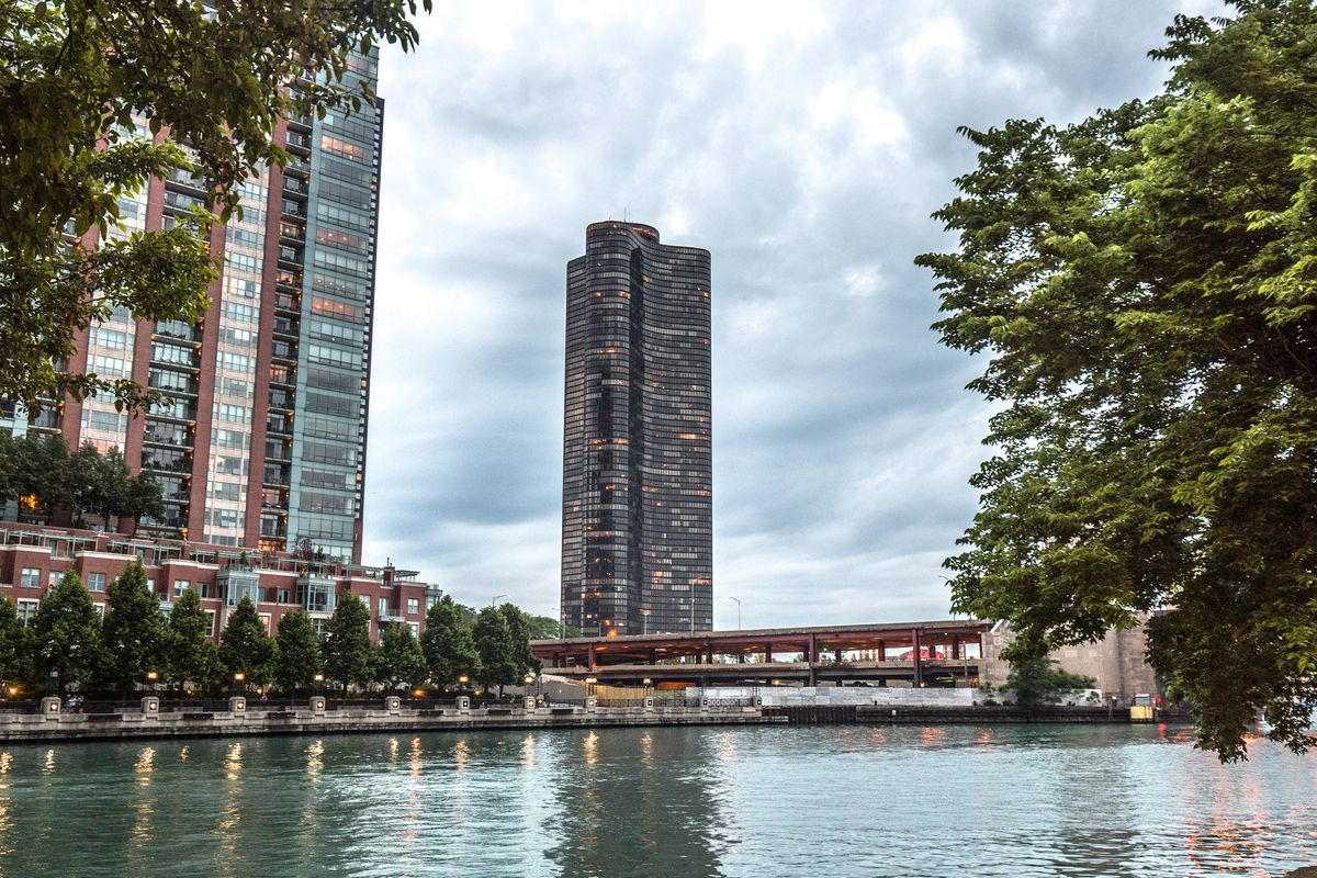 A tall black tower sits on the edge of a lake. In the foreground there is water and a bridge. Trees are on both sides.
