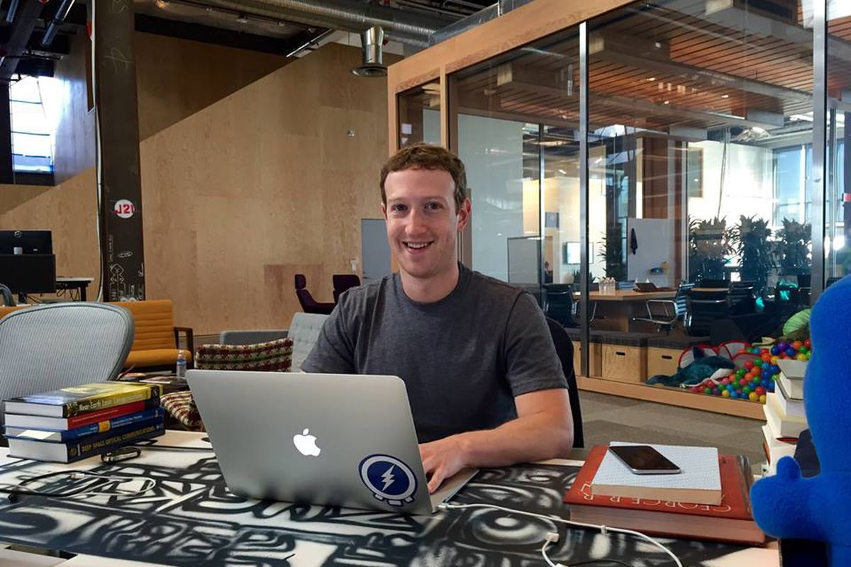 Facebook CEO Mark Zuckerberg sits at a table and ties on a laptop.