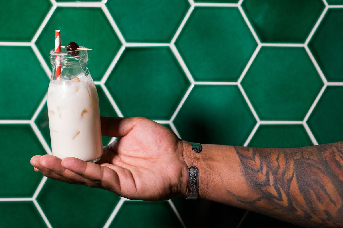 a tattooed arm holding a milky-looking drink in front of a wall of green tiles
