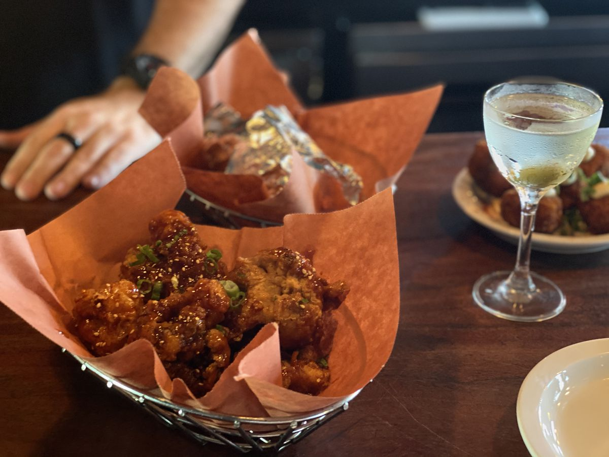 A paper-lined basked of chicken wings, another basked behind it, and a martini on a wood bar with a server standing nearby