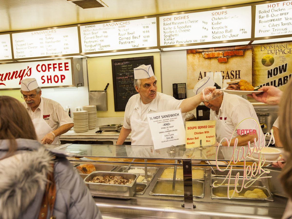 Two men in white aprons and paper hats hand dishes to customers from behind a deli counter.
