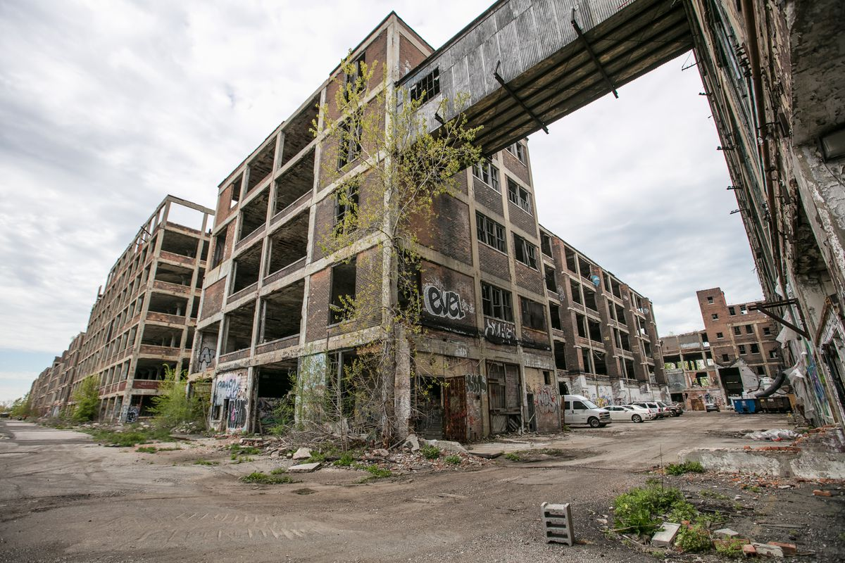 A huge, abandoned warehouse and factory. All the windows are empty, there's graffiti on the side of the brick building, and debris on the dirt nearby.