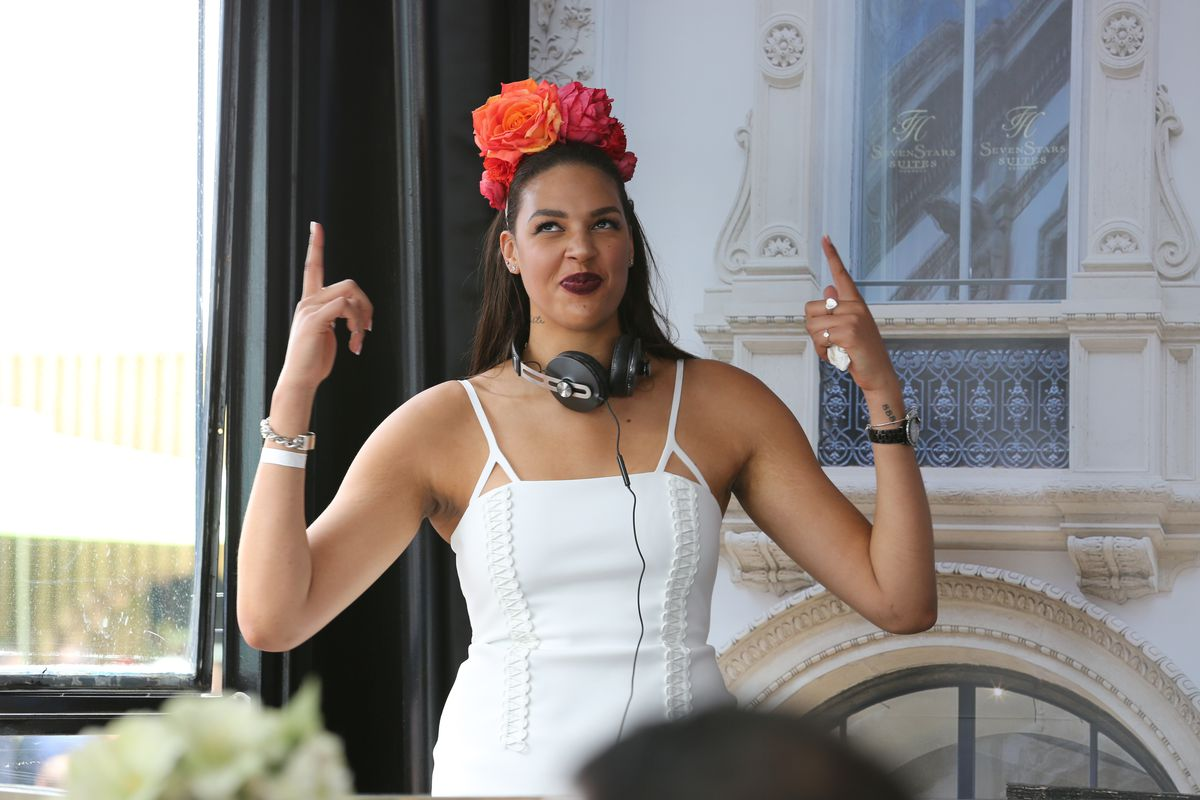 Liz Cambage with headphones around her neck, pointing up at red flowers in her hair