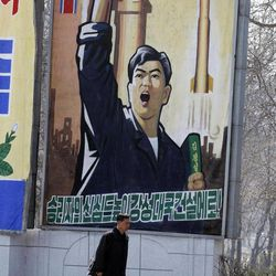 """A North Korean man walks past a propaganda billboard in Pyongyang, North Korea, Friday, April 13, 2012. North Korea's much-anticipated rocket launch ended quickly in failure early Friday, splintering into pieces over the Yellow Sea soon after takeoff, according to South Korean and U.S. officials. The slogan reads """"Let's raise the spirits of winners and build a strong and prosperous nation!"""""""