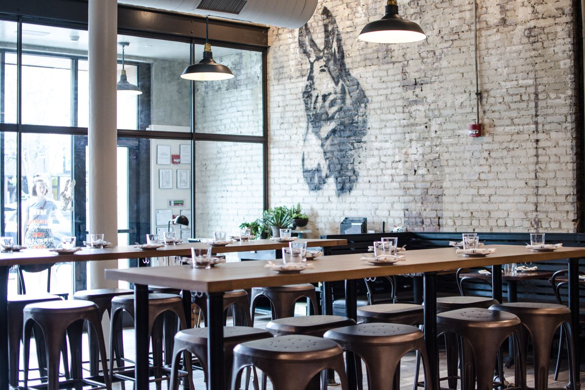 A donkey mural on painted brick appears above high-top seating in the foreground at Little Donkey