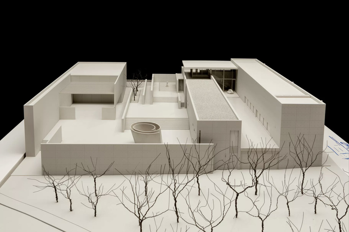 A scale model of a rectangular building with a multilevel roof and cut-outs, creating interior courtyards.