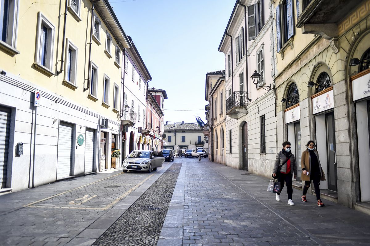 Two women walk in the town of Codogno, in the region of Lombardia, northern Italy, Wednesday, March 11, 2020.