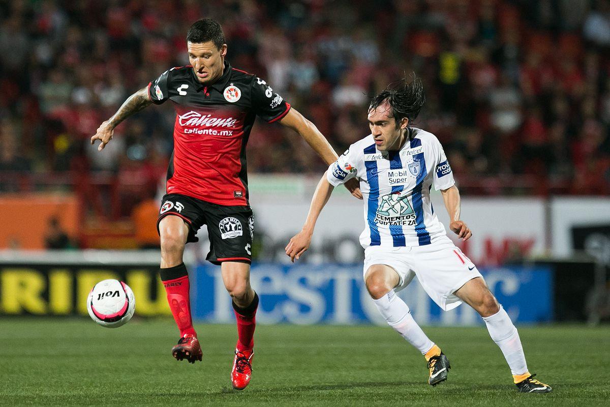 "Tijuana's Damián Musto and Pachuca's Joaquín ""Shaggy"" Martínez fight for a loose ball."