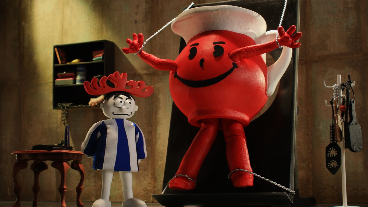 the hawaiian punch guy stands alongside Kool-Aid man, who is strung up on a torture rack