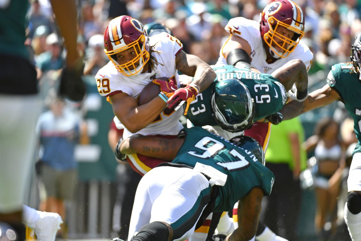 Washington running back Derrius Guice is tackled by Philadelphia Eagles defensive tackle Malik Jackson and outside linebacker Nigel Bradham during the second quarter at Lincoln Financial Field.