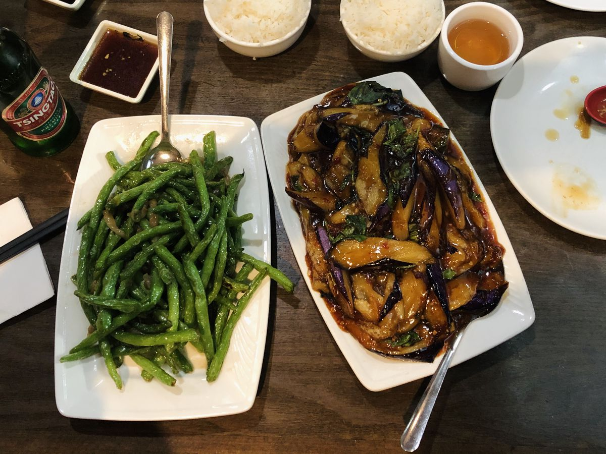 A plate of sauteed string beans sits beside a plate of spicy eggplant. They are accompanied by two bowls of rice and various sauces.