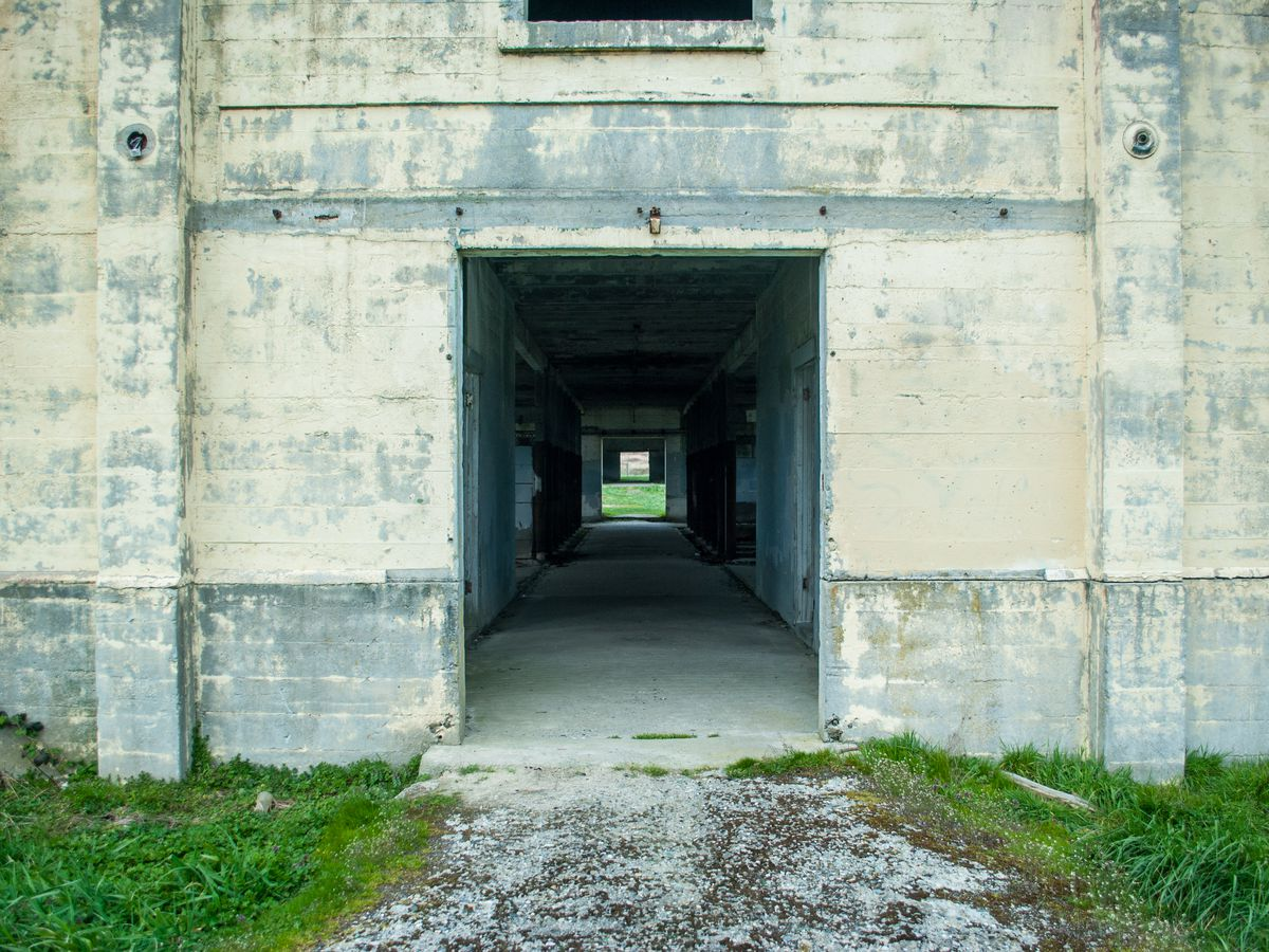 A wall of a stone building in ill repair. A corridor runs through the center through an open doorway reaching light on the other side.