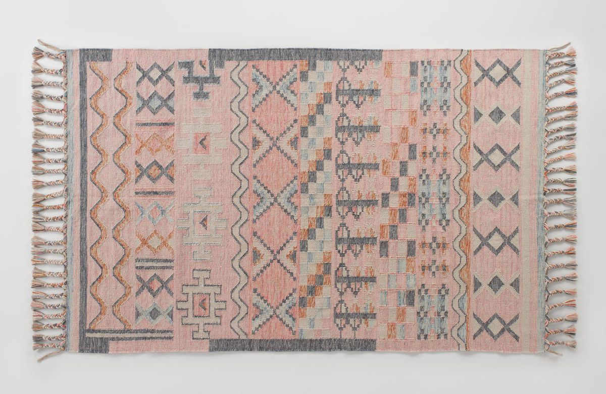 A woven rug with a pink and grey pattern and tassels.