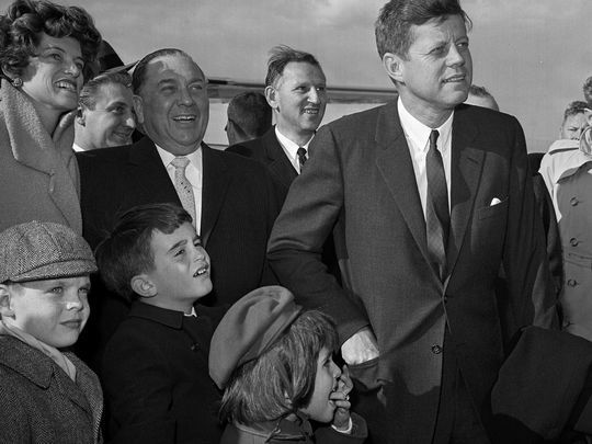 In this April 28, 1961, photo, President John F. Kennedy stands during a welcoming ceremony at O'Hare Airport as Mayor Richard J. Daley looks on, with Kennedy's sister Eunice Kennedy Shriver, at left, and some of her children. | AP
