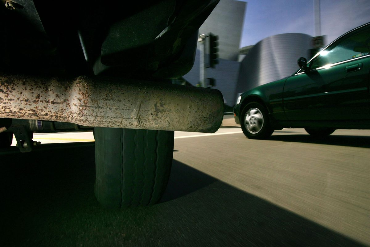 The tailpipe of a vehicle pumping out greenhouse gas emissions is seen next to another car in Los Angeles, CA.