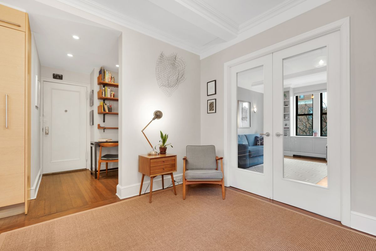A foyer with a rug, light grey walls, beamed ceilings and French doors that lead to another room.