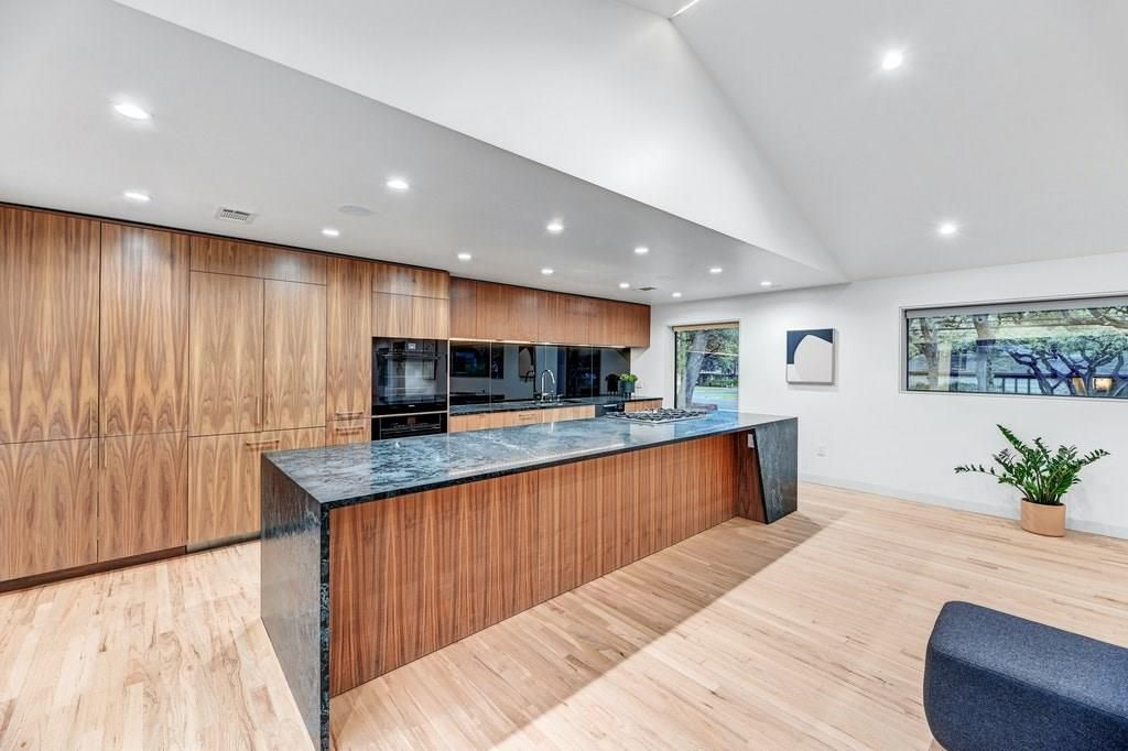 An open kitchen with a long, marble-topped island with a recessed wood side underneath with a pattern that echoes a wall of wood cabinets behind it.