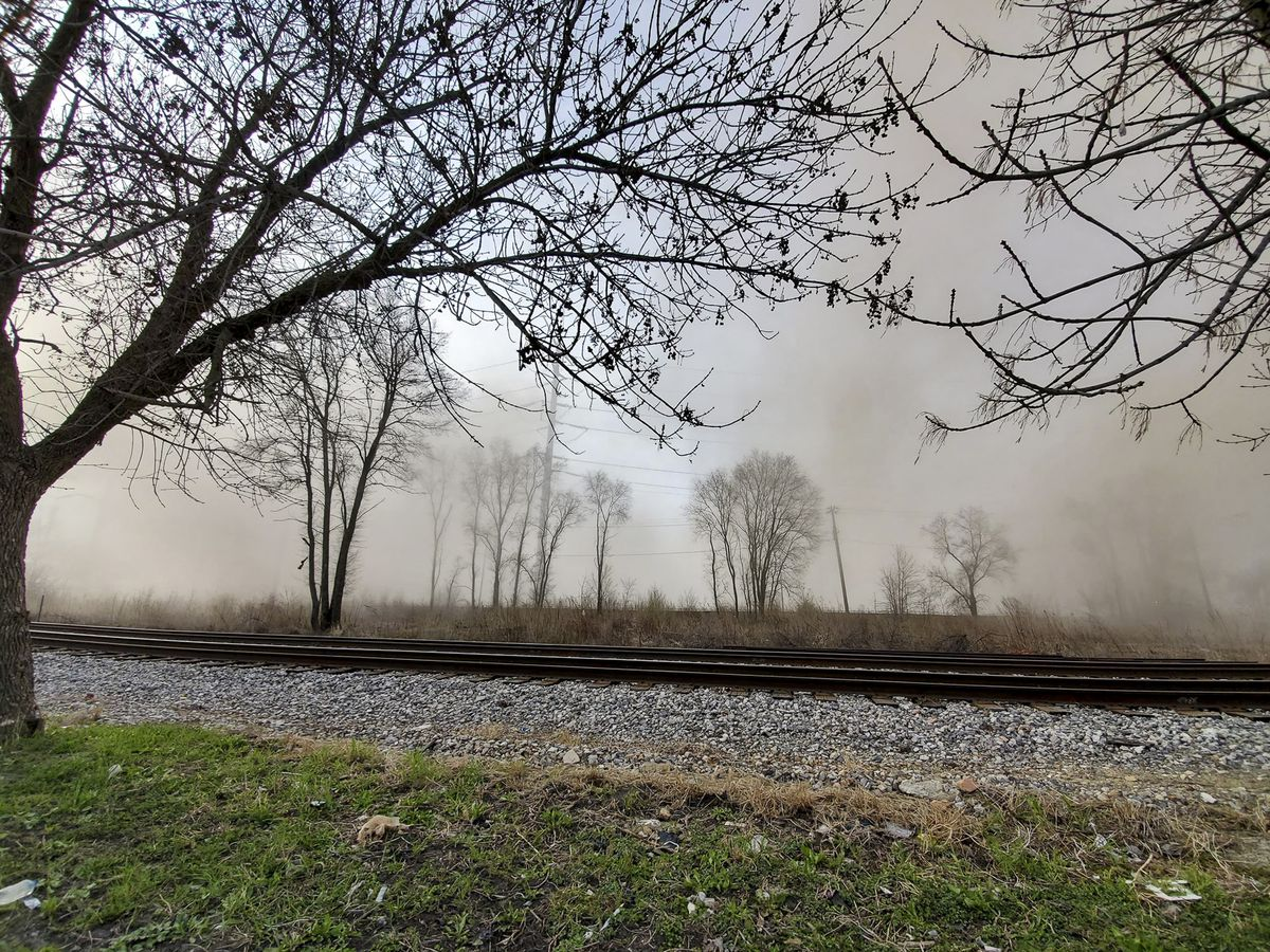 A cloud of dust spreads across the Little Village neighborhood after the Crawford power plant smokestack was imploded on Saturday.