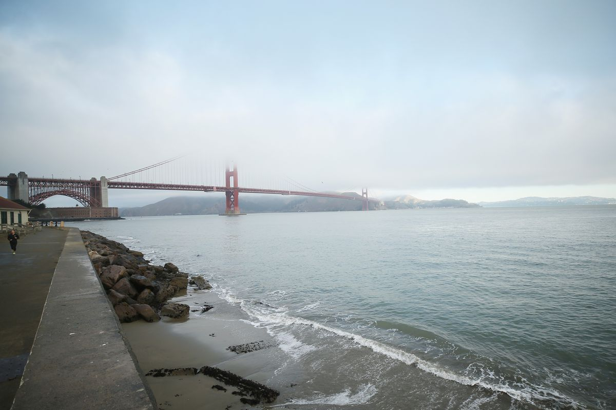 The Golden Gate Bridge appearing very small in the distance, mostly clouded with fog.