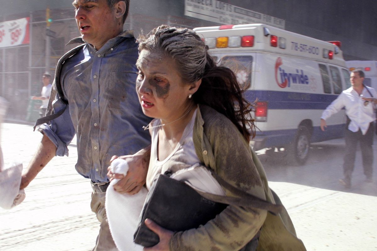 People flee the scene near New York's World Trade Center after terrorists crashed two planes into the towers Tuesday, Sept. 11, 2001.