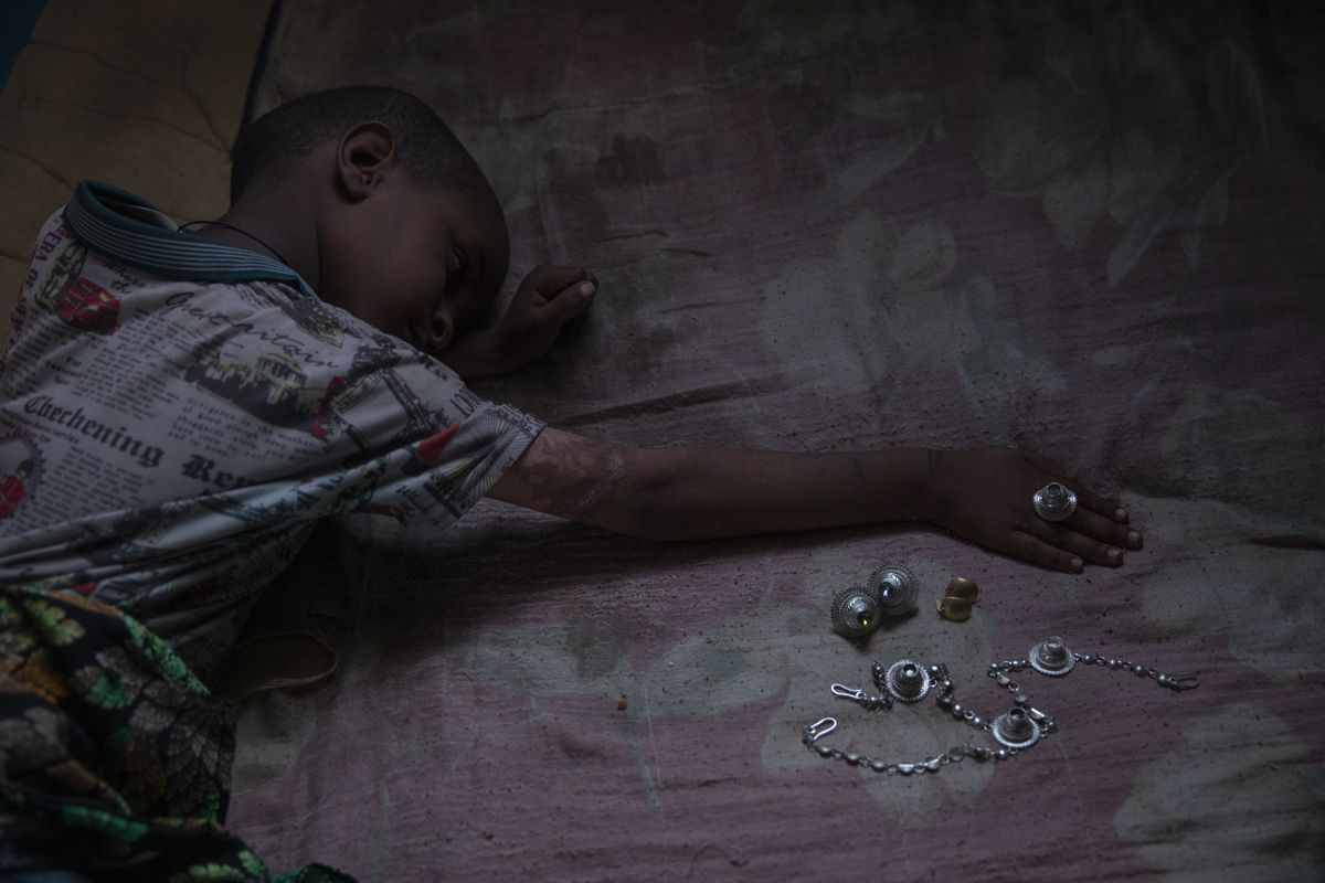 Micheale Gebremariam, 5, a Tigrayan refugee, plays with jewelry belonging to his deceased mother Letay.