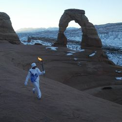 Native American Stephanie Laree Spann walks the Olympic torch past Delicate Arch in Arches National Park near Moab on Feb. 2, 2002.