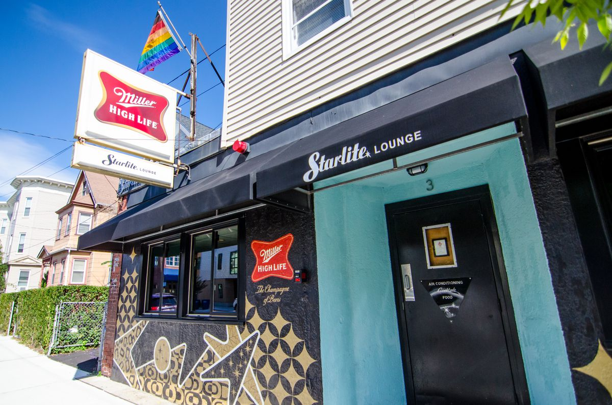 The exterior of Somerville restaurant Trina's Starlite Lounge features turquoise, black, and gold paint, Miller High Life signage, and a rainbow flag