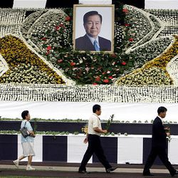 Mourners walk with flowers in front of a portrait of the late former South Korean President Kim Dae-Jung during a memorial service at Seoul Plaza in Seoul, South Korea, Wednesday.