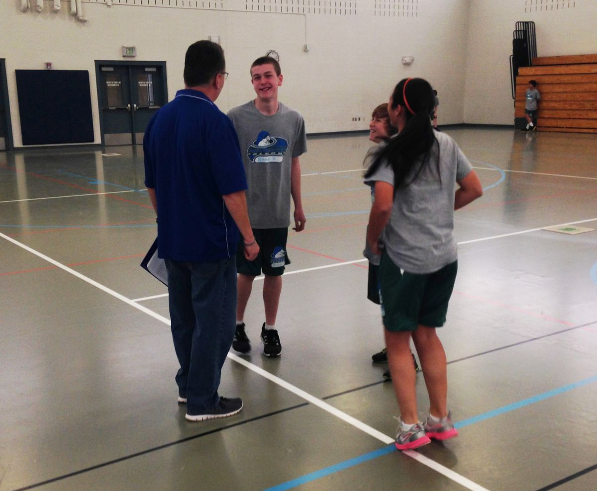 Students jog in place while chatting with P.E. teacher Allyn Atadero before class begins.