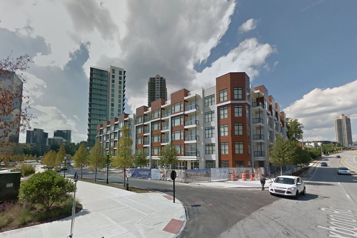 A five-story modern apartment complex, across from a new park.