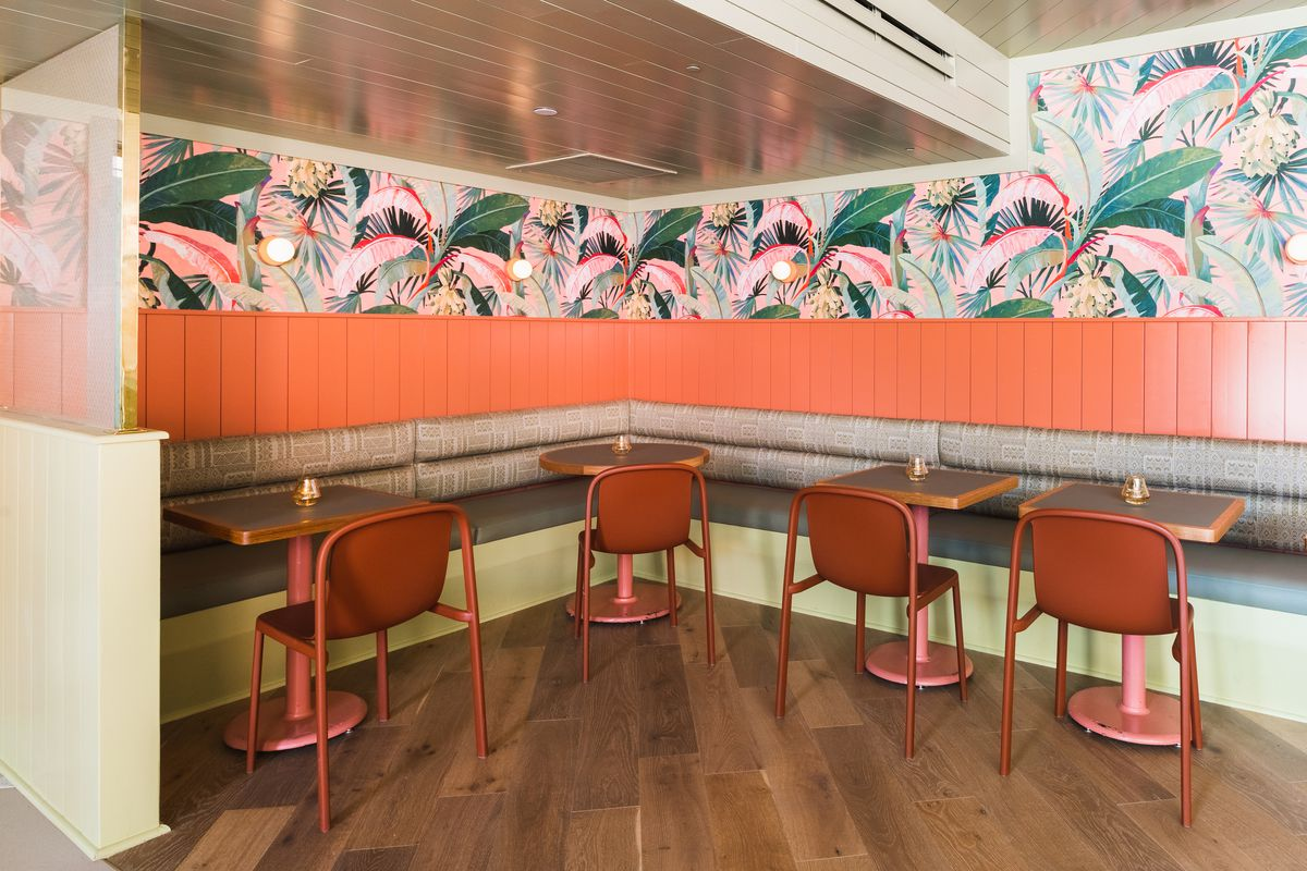 Little Palm's dining room featuring frond wallpaper and coral-color banquettes and chairs.