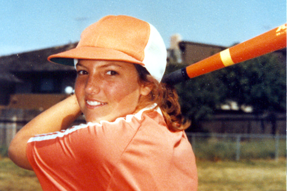 A 13-year-old in an orange softball uniform poses formally at bat.