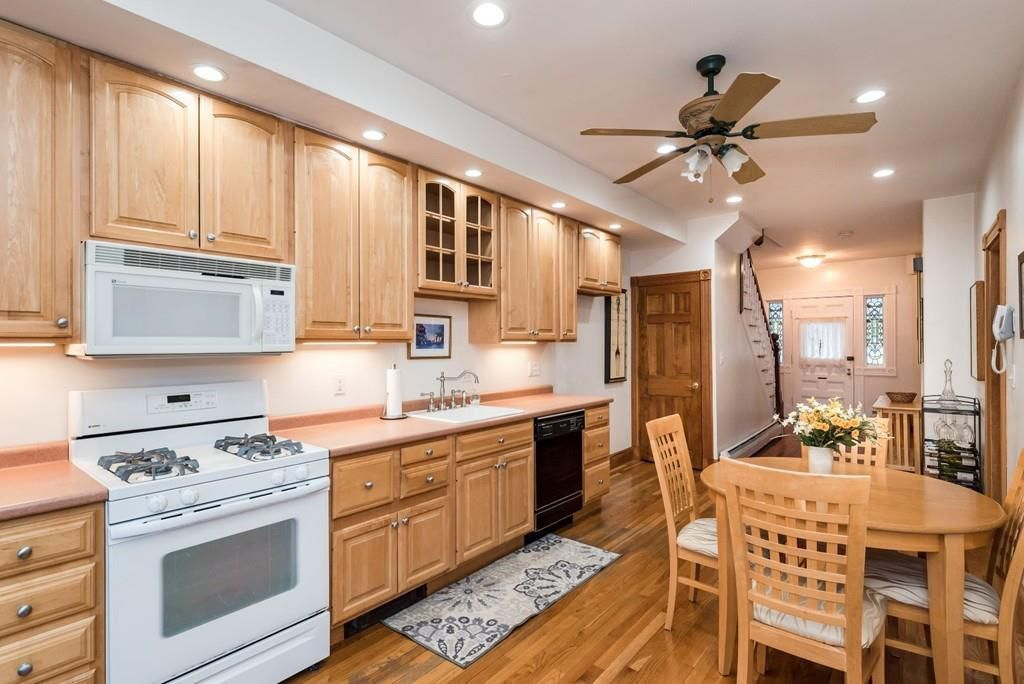 A kitchen with a table and four chairs, and there's one long counter and a ceiling fan.
