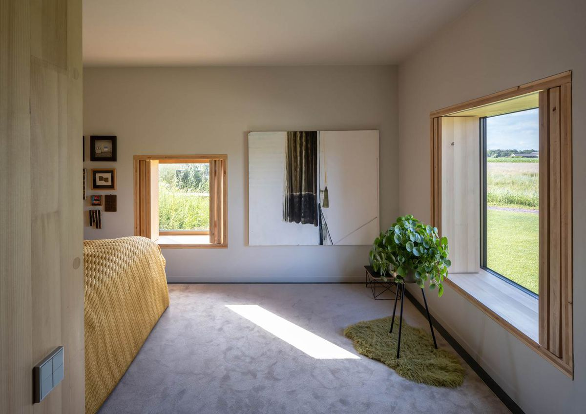 Bedroom with square windows, gray carpet, and the peek of a yellow bed around the corner.