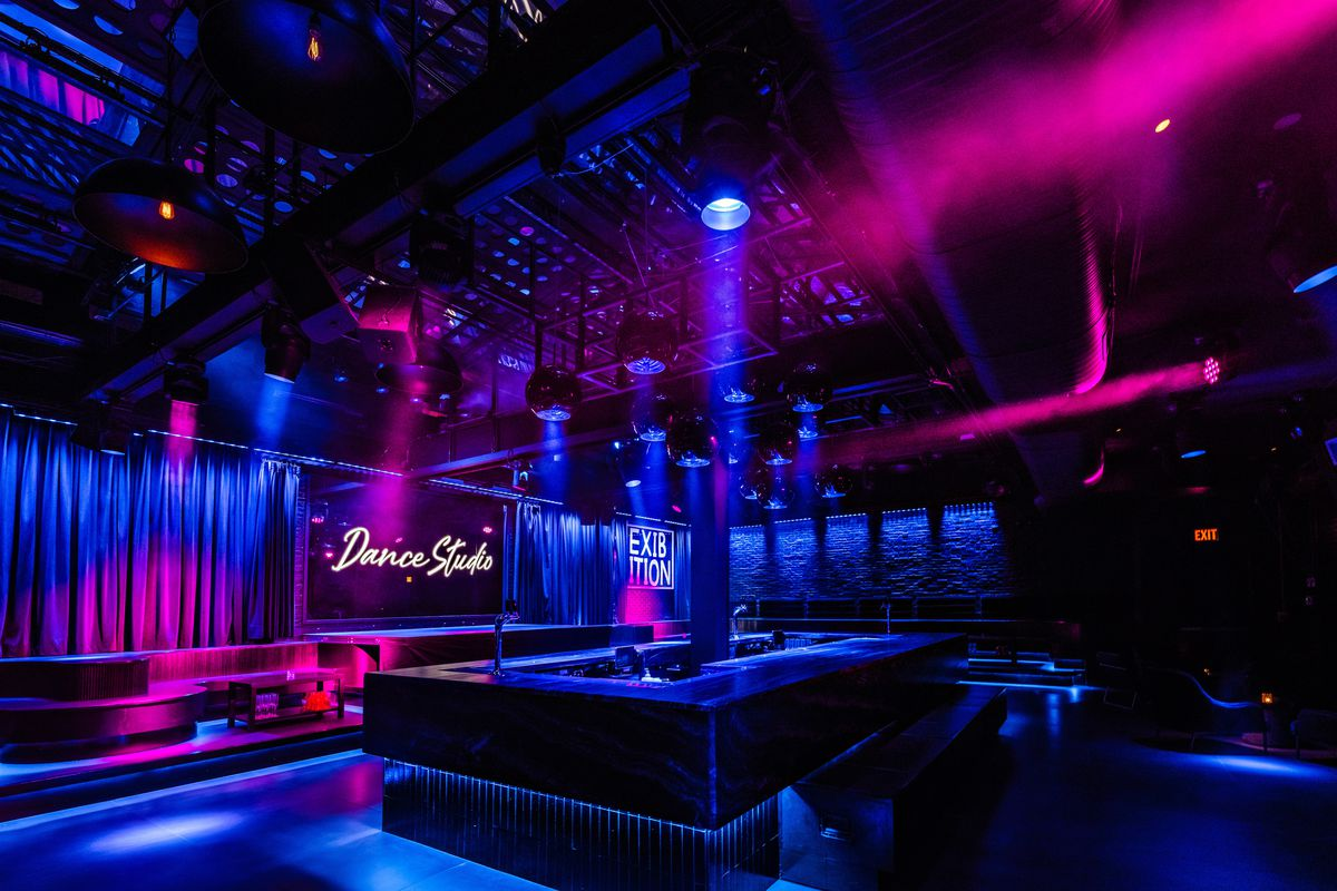 A dark dance floor with lots of red, and purple accent lights.