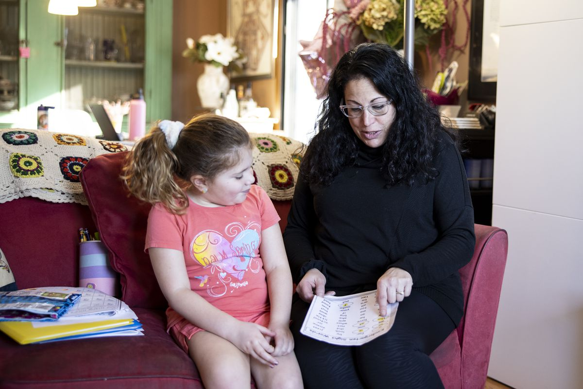 Sarah Warren reads to her daughter, Raya, from a school worksheet while doing online learning during the COVID-19 pandemic.