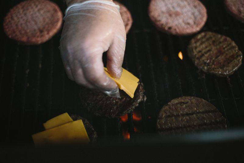 A hand putting slices of orange cheese on grilling burgers