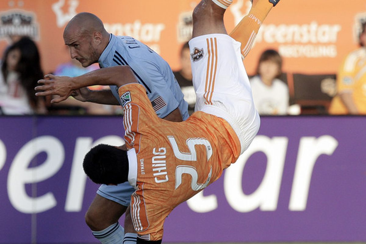 HOUSTON - JULY 16:  Brian Ching #25 of the Houston Dynamo is updended by Aurelien Collin #78 of the Sporting KC in the first half at Robertson Stadium on July 16, 2011 in Houston, Texas.  (Photo by Bob Levey/Getty Images)