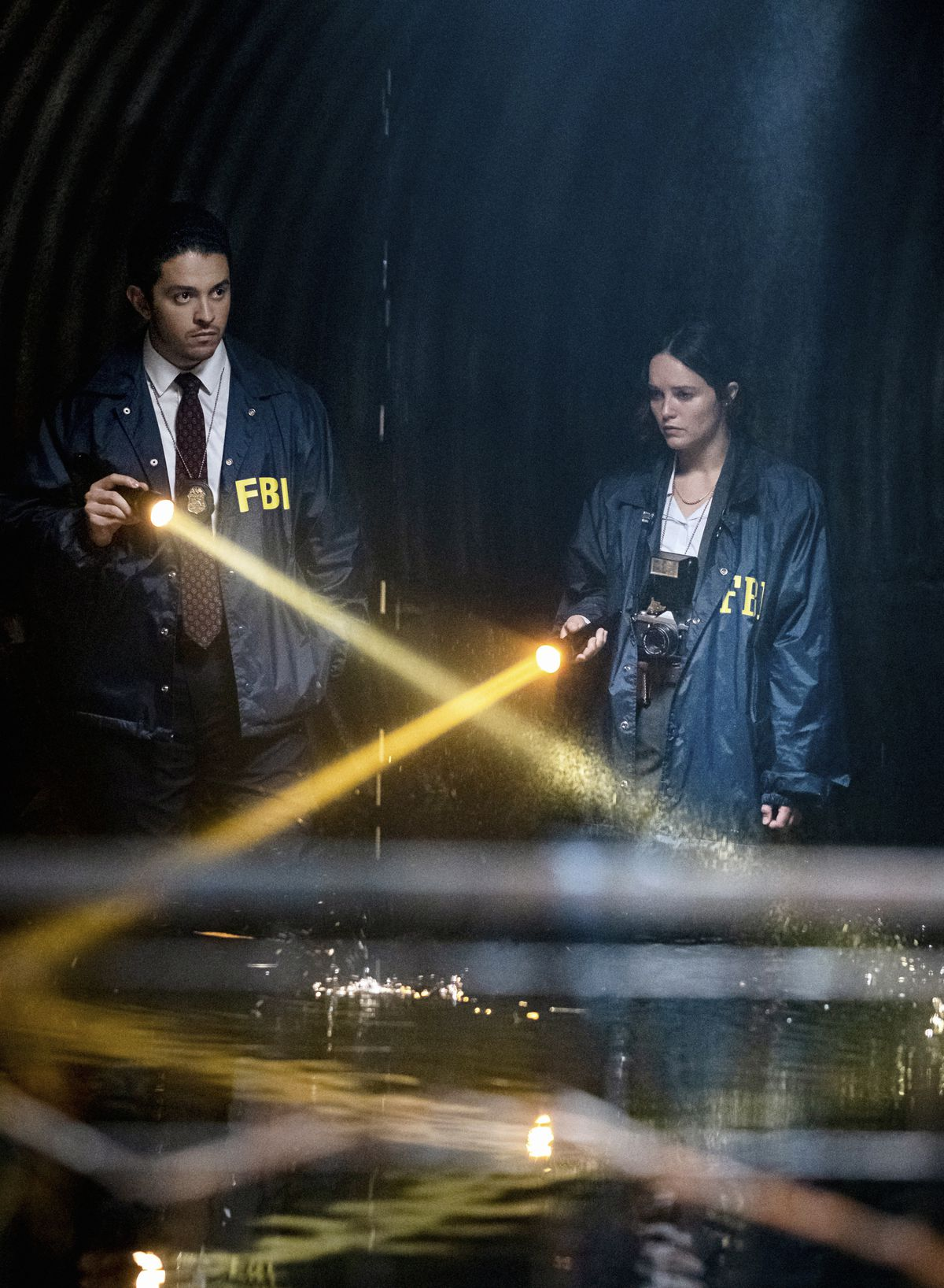 Clarice Starling and fellow FBI agent Tomas Esquivel shine flashlights over water in a dark space in Clarice.