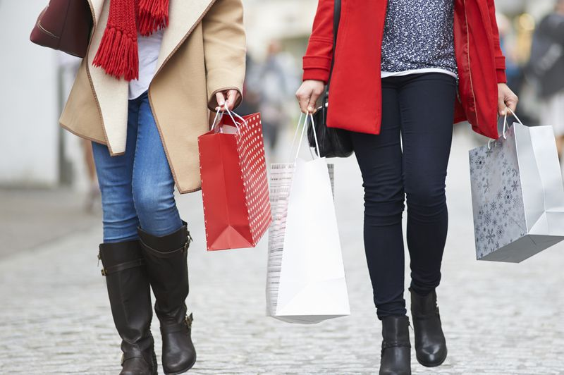 Women carrying red and white shopping bags