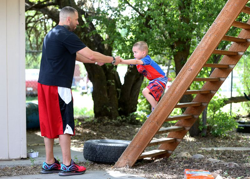John Chapman helps son Braxton off some stairs in their backyard in Holladay home on Friday, June 5, 2020.