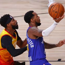 Monte Morris, right, of the Denver Nuggets, drives past Mike Conley, left, of the Utah Jazz during the first half of Game 4 of an NBA basketball first-round playoff series, Sunday, Aug. 23, 2020, in Lake Buena Vista, Fla.