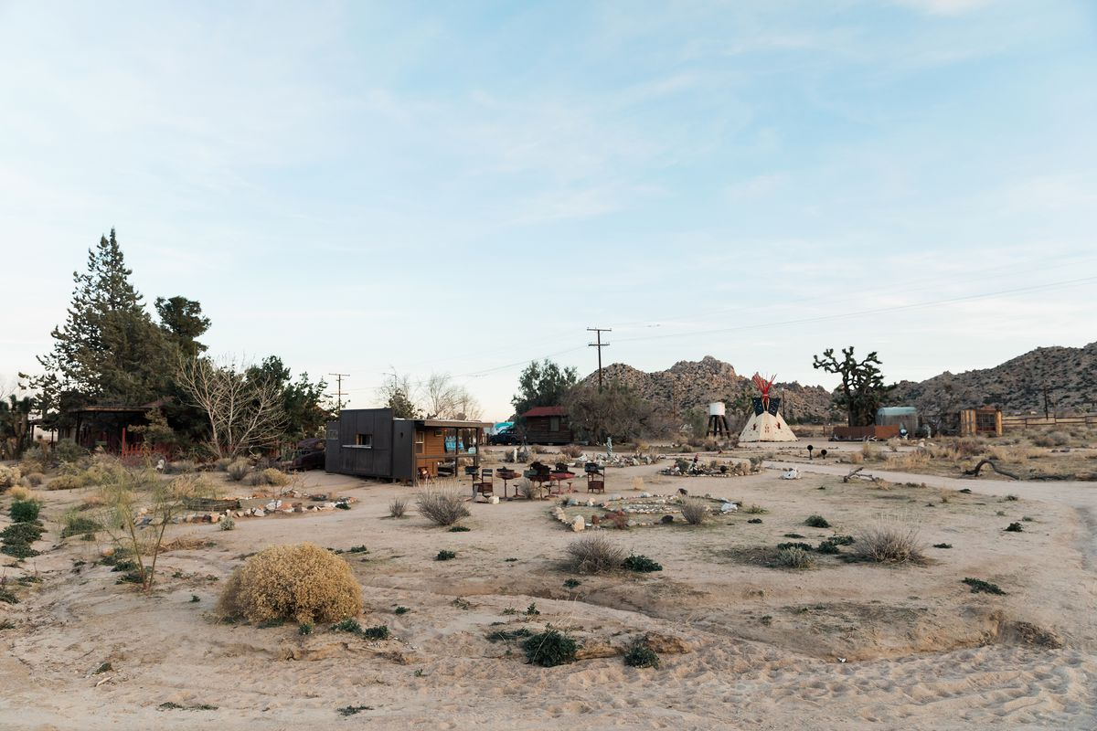 In the foreground is desert. In the distance are a group of houses.