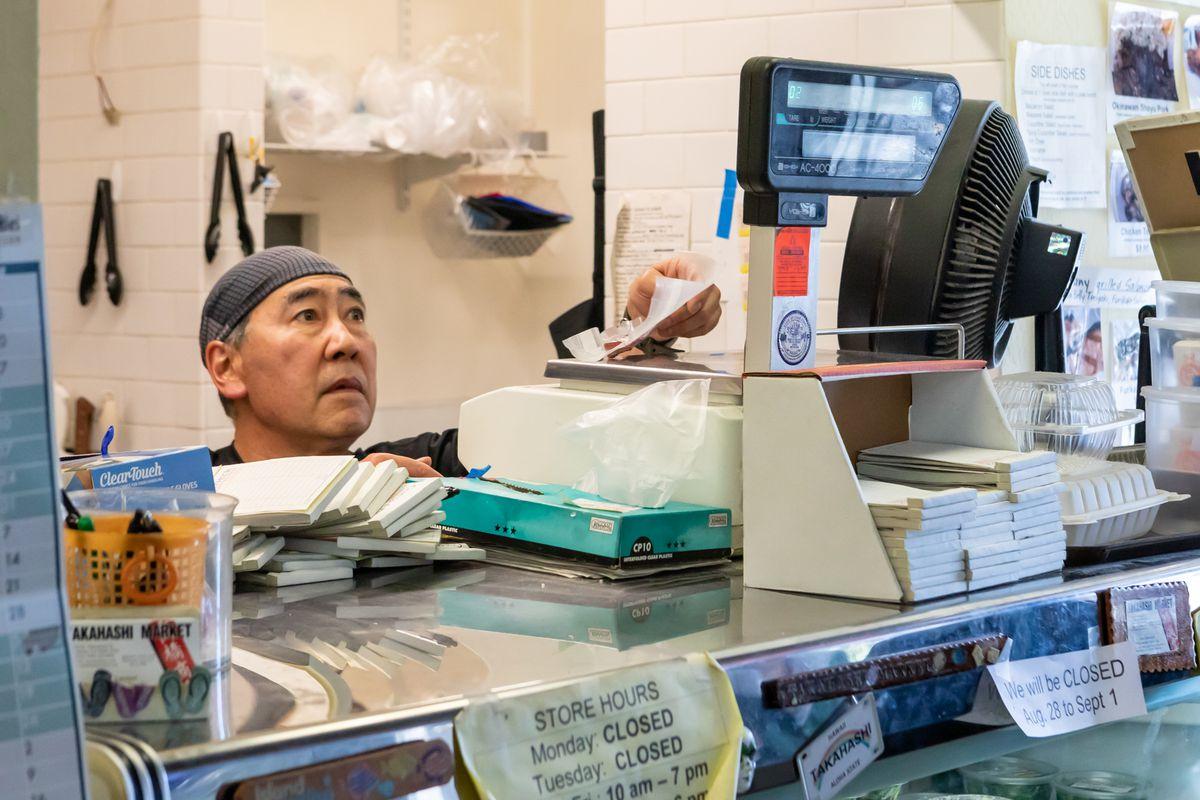 A man behind the counter at the Takahashi Market