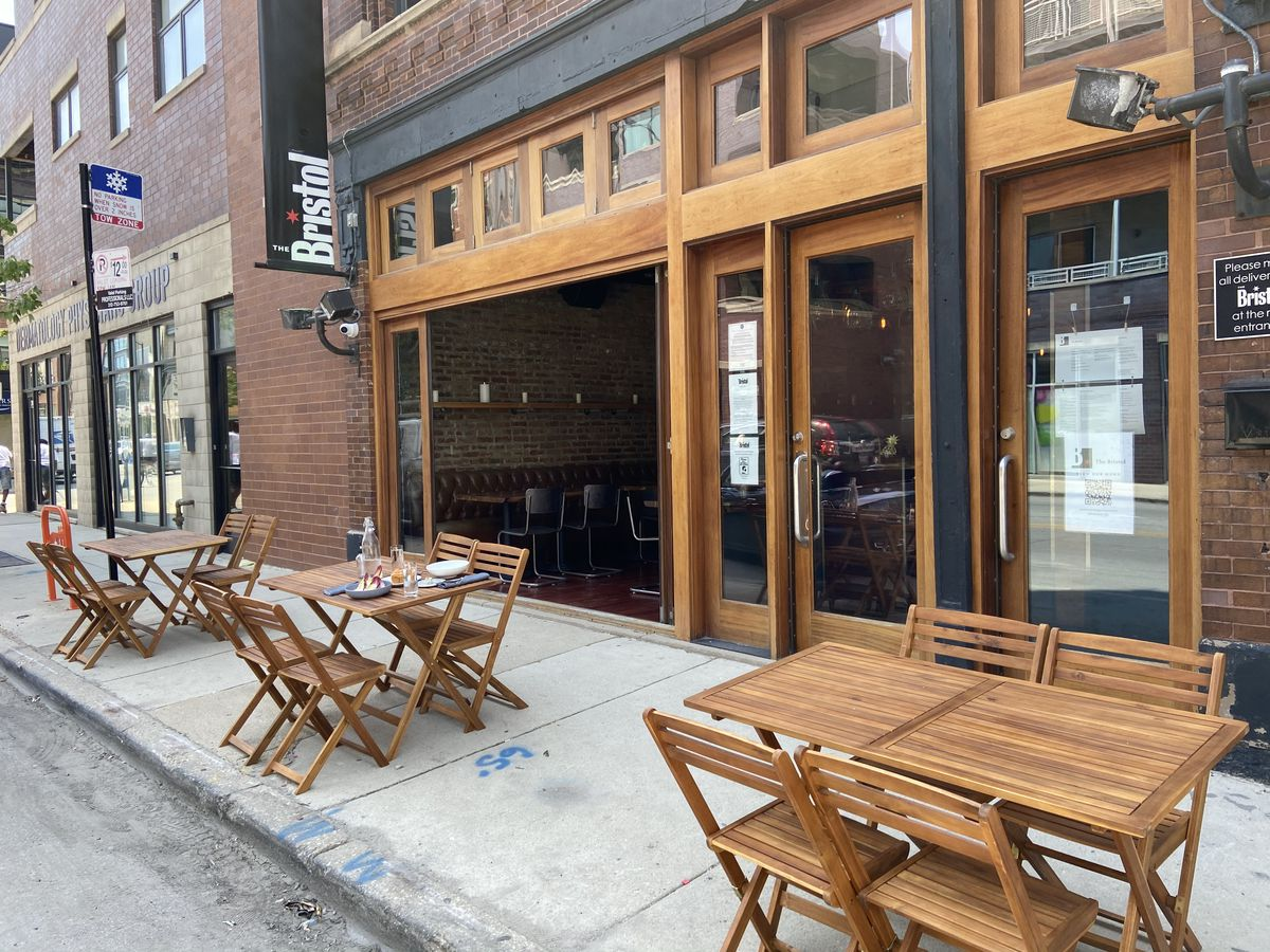 A sidewalk cafe with tables and chairs outside a restaurant.