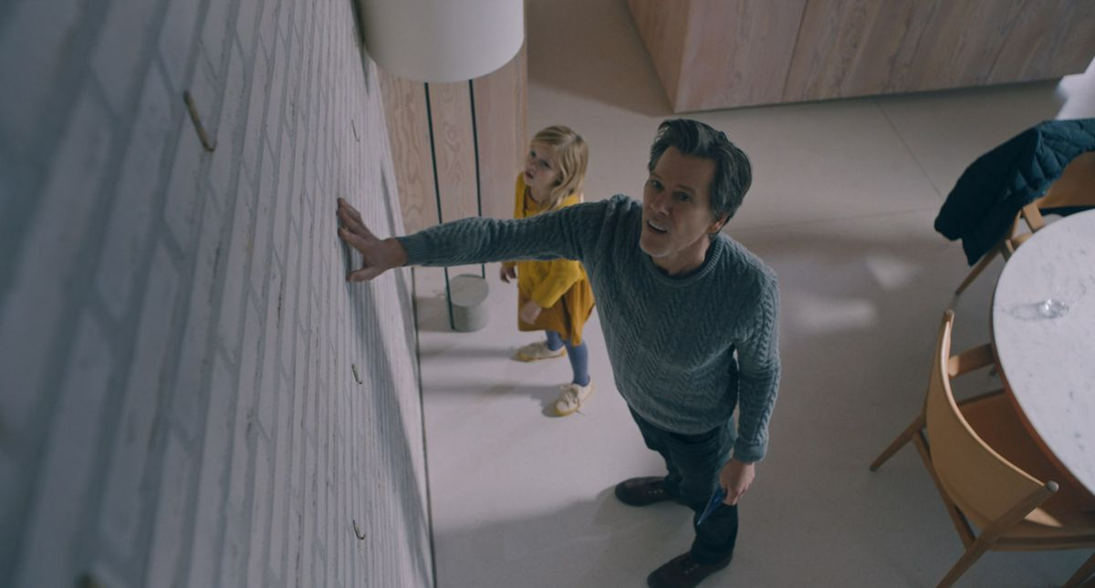 In a high overhead shot, Kevin Bacon and Avery Essex examine a normal wall with abnormal concern in You Should Have Left.
